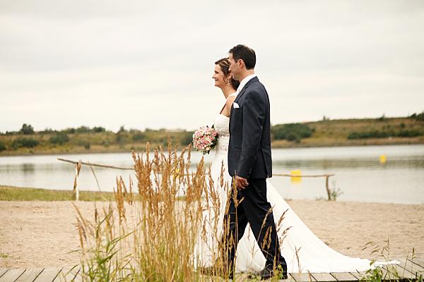 Hochzeitsfoto laufendes Brautpaar am See.
