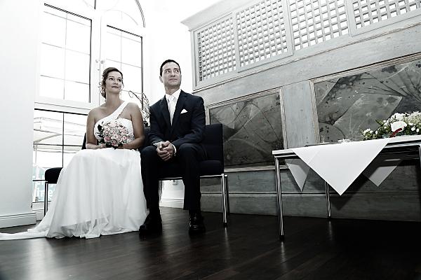 Low Key Hochzeitsfoto sitzendes Brautpaar.