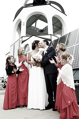 Hochzeitsfoto küssendes Brautpaar vor Turm mit Blumenkindern in roten Kleidern.