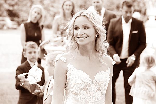 Low Key Hochzeitsfoto Braut im Vordergrund, Bräutigam und Blumenkinder im Hintergrund.