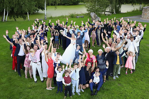 Hochzeitsfoto Brautpaar mit Familie auf Wiese.
