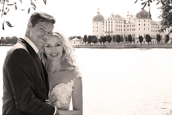 Low Key Hochzeitsfoto Brautpaar vor Schloss.