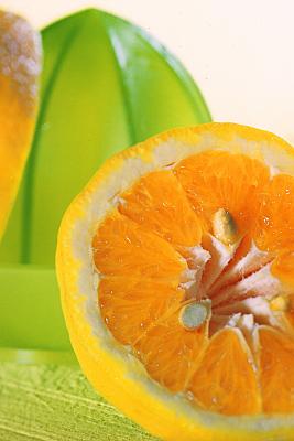 Werbefoto angeschnittene Orange und grüne Sternenfrucht vor hellem Hintergrund.