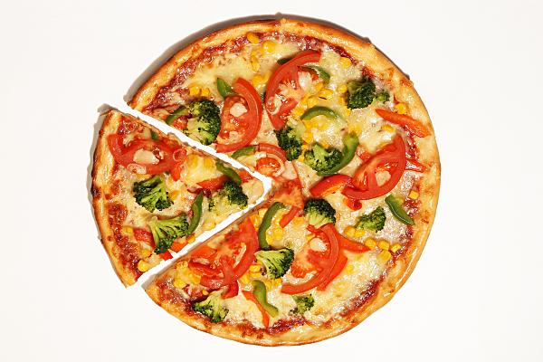 Werbefoto angeschnittene Pizza mit Belag vor hellem Hintergrund.