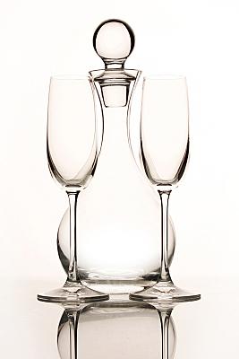 Werbefoto Glaskrug mit Glaspfropfen im Hintergund mit zwei davor stehenden Sektkelchen vor hellem Hintergrund.