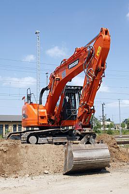 Bilddokumentation oranger Bagger auf Baustelle.
