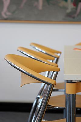 Bilddokumentation Raumeinrichtung mit gelb-silbernen Freischwinger-Stühlen.