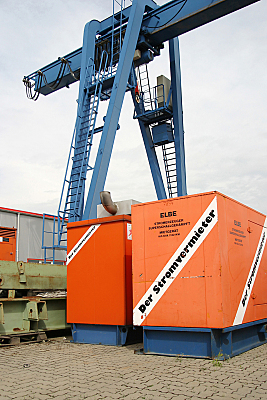 Bilddokumentation blauer Kran über Containern.