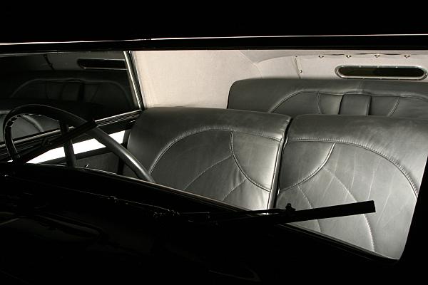 Low Key Werbefoto eines Oldtimer-Wagens durch die Frontscheibe auf die Ledersitze.