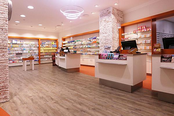 Architekturfoto Apotheke mit Backsteinsäulen und weiß-orangen Regalen sowie Holzfußboden.