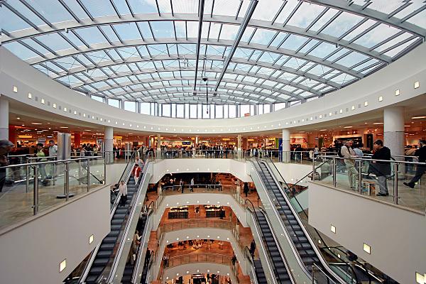 Architekturfoto modernes, großes Einkaufszentrum mit Glaskuppel und Rolltreppen in der Mitte.