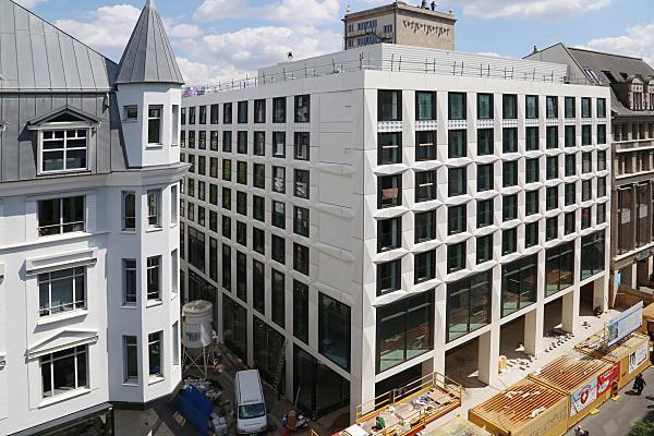 Architekturfoto Baustelle Eckgebäude mit Baufahrzeugen, Silo und gegenüberliegendem Eckgebäude..