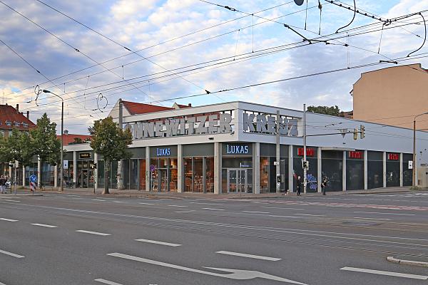 Architekturfoto Discounter-Eckgebäude mit Ladengeschäften und Leuchtreklame sowie vorgelagerter Straße und Passanten.