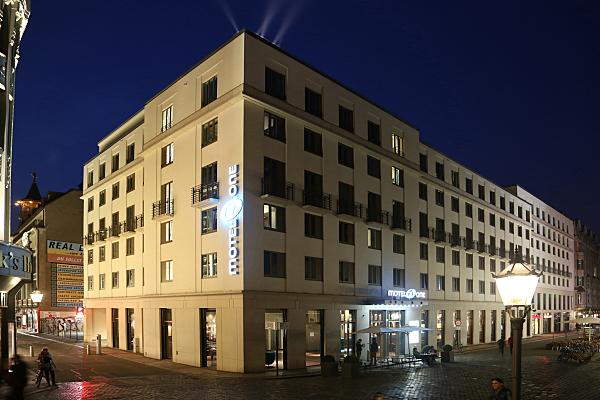 Architekturfoto Hotel-Eckgebäude mit Leuchtreklame, vorgelagerter Straße sowie Passanten bei Nacht.