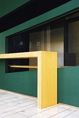 Architekturfoto gelber Tresen vor grüner Wand mit Fenster.