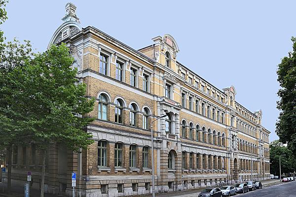 Architekturfoto Klinker-Hausfassade mit vorgelagerter Straße und parkenden Autos.
