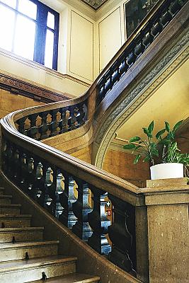 Architekturfoto gewundene Steintreppe mit verziertem Geländer und lichtdurchflutetem Fenster.