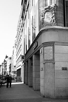 Schwarz-weiß Architekturfoto Fassadendetail Hausecke mit Reliefaufsatz und Säulenschmuck.