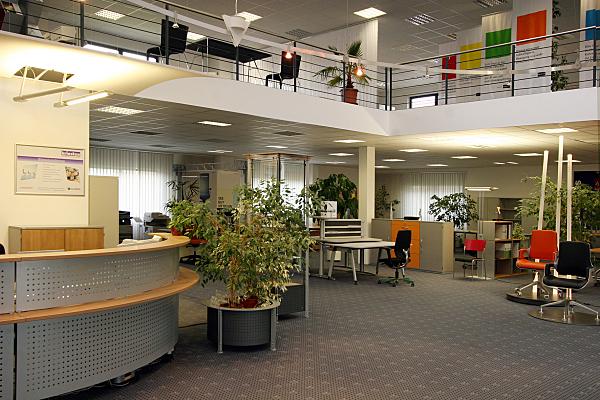 Architekturfoto Großraumbüro mit grauem Empfangsbereich, Sitzplätzen auf einer Galerie sowie Schreibtischen und niedrigen Regalen im Hintergrund.