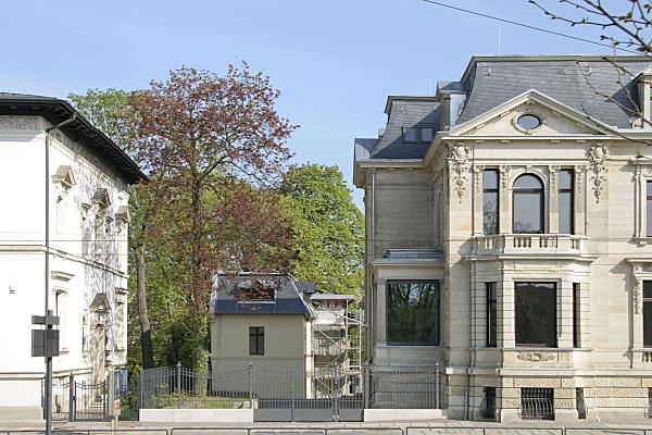 Architekturfoto beigefarbene Gründerzeitvilla mit Zaunelementen im Vordergrund sowie kleinem Hinterhaus und Bäumen im Hintergrund.