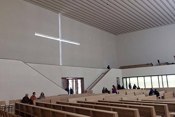 Architekturfoto Kircheninnenraum mit Lichtkreuz im Mauerwerk, Sitzreihen und Treppenaufgang sowie einigen Personen.