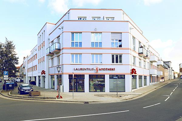 Architekturfoto Eckhaus und vorgelagerte Straße mit Fokus auf Apothekengeschäft im Erdgeschoss.