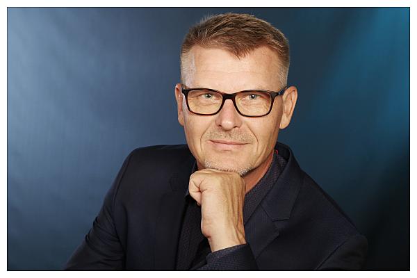Bewerbungsfoto im Studio auf dem blauen Hintergrund von einem Mann, der auf seiner Hand abtützt