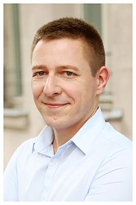 Bewerbungsfoto von einem Mann draussen, welcher in die Kamera lächelt