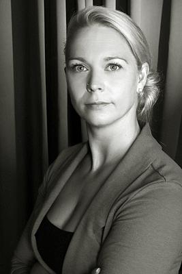 Businessfoto in schwarz-weiss von einer Dame, die direkt in die Kamera guckt
