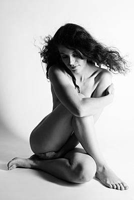 Aktfoto schwarz-weiss von einer jungen Dame, welche sich umarmt und nach unten guckt