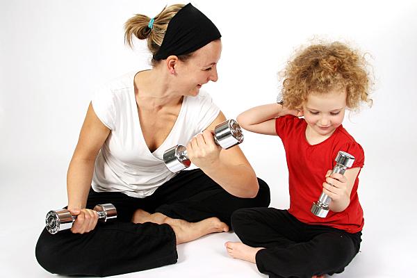 Foto von Mama und Kind, die zusammen Sport machen
