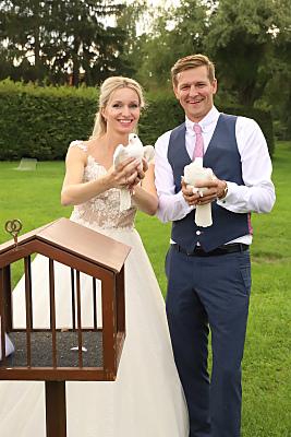 Hochzeitspaarfoto, welches Tauben in den Händen trägt