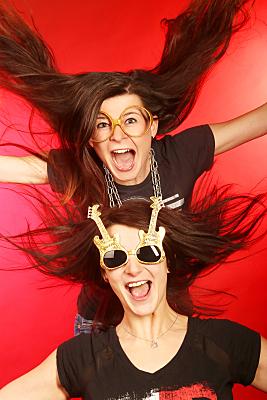 Verrücktes Friendsfoto auf dem roten Hintergrund, wo beide Mädchen schreien aus Spass